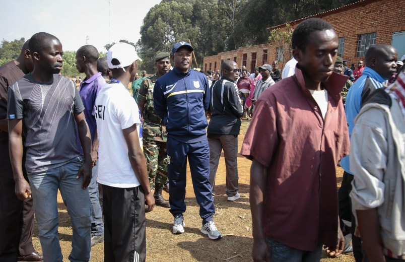 President Pierre Nkurunziza, center, waits in line to cast his vote for the presidential election, in Ngozi, Burundi Tuesday, July 21, 2015. Burundi began voting in its disputed presidential election Tuesday with low turnouts in the capital following a night of explosions and gunfire in opposition strongholds where residents oppose President Pierre Nkurunziza's bid for a third term. (AP Photo/Berthier Mugiraneza)