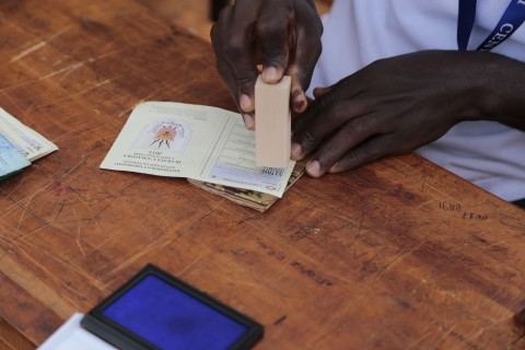 A Burundian official stamps after checking the voting card of a voter before he casts his ballot in parliamentary elections in Ngozi, Burundi, Monday, June 29, 2015.  Burundians are voting in parliamentary elections marked by an opposition boycott and the threat of violence as police battle anti-government protesters in the capital. (AP Photo/Gildas Ngingo).
