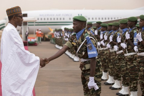 epa04781877 Nigerian President Muhammadu Buhari (L) shakes hands with a Niger officer during his arrival in Niamey, Niger, 03 June 2015. This is the first official working visit for the newley elected Nigerian President Muhammadu Buhari. According to reports one of the main areas of discussion between the two presidents was their joint fight against Islamic militant group Boko Haram and areas of collaboration to this end.  EPA/STR
