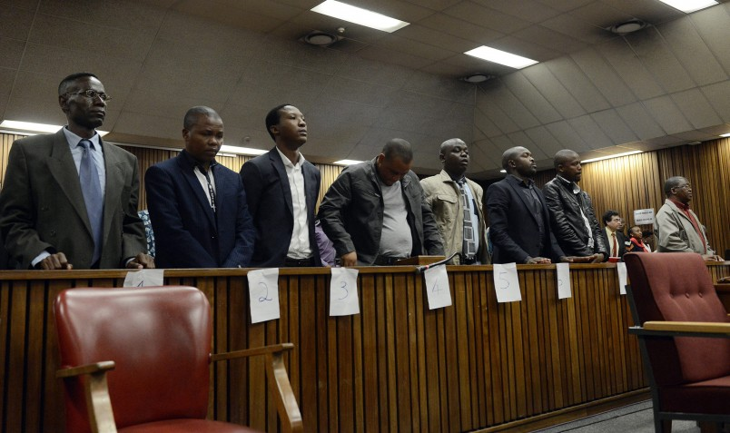 Former policemen, from left, Meshack Malele, Thamsanqa Ngema, Percy Mnisi, Bongamusa Mdluli, Sipho Ngobeni, Lungisa Gwababa, Bongani Kolisi and Linda Sololo stand in the dock prior to judgment in the High Court in Pretoria, South Africa, Tuesday, Aug. 25, 2015. The eight were found guilty for the murder and assault of Mozambican taxi driver, Mido Macia, who died of his injuries after being handcuffed to a police vehicle and dragged along a street in Daveyton, east of Johannesburg in 2013. The eight will be sentenced on September 22. (AP Photo)