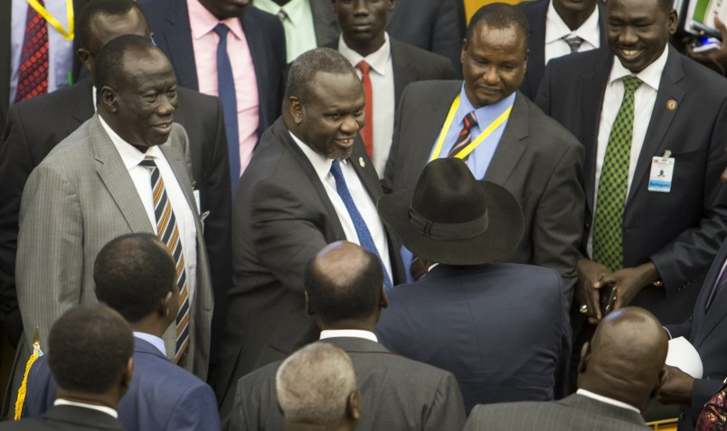 South Sudan's rebel leader Riek Machar, center, shakes hands with South Sudan's President Salva Kiir, center-right wearing a black hat, after lengthy peace negotiations in Addis Ababa, Ethiopia Monday, Aug. 17, 2015. South Sudan's President Salva Kiir refused to sign a peace agreement Monday with rebel forces, saying he needs 15 days before he will sign, although rebel leader Riek Machar had signed the accord before Kiir refused. (AP Photo/Mulugeta Ayene)