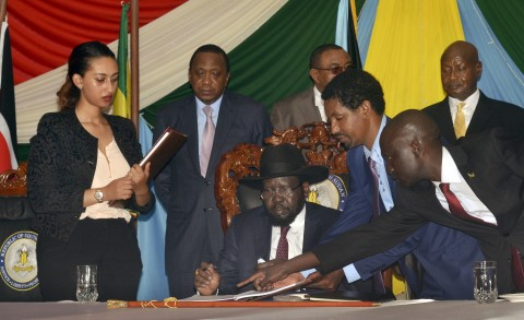 South Sudan President Salva Kiir, seated, signs a peace deal, as Kenya's President Uhuru Kenyatta, center-left, Ethiopia's Prime Minister Hailemariam Desalegn, center-right, and Uganda's President Yoweri Museveni, right, witness the signing while standing behind, in the capital Juba, South Sudan Wednesday, Aug. 26, 2015. Kiir on Wednesday signed a peace deal with rebels, more than 20 months after the start of fighting between the army and rebels led by his former deputy Riek Machar. (AP Photo/Jason Patinkin)