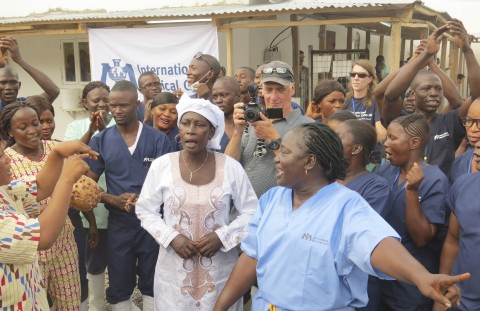 Adama Sankoh, 40, centre,  who contracted Ebola after her son died from the disease late last month stands with health officials the moment after she was discharge from Mateneh  Ebola treatment center outskirt of Freetown, Sierra Leone, Monday, Aug. 24, 2015, Health authorities in Sierra Leone released the country's last known Ebola patient from the hospital on Monday, a milestone that allows the nation to begin a 42-day countdown to being declared free of the virus that has killed nearly 4,000 people here. (AP Photo/Alie Turay)