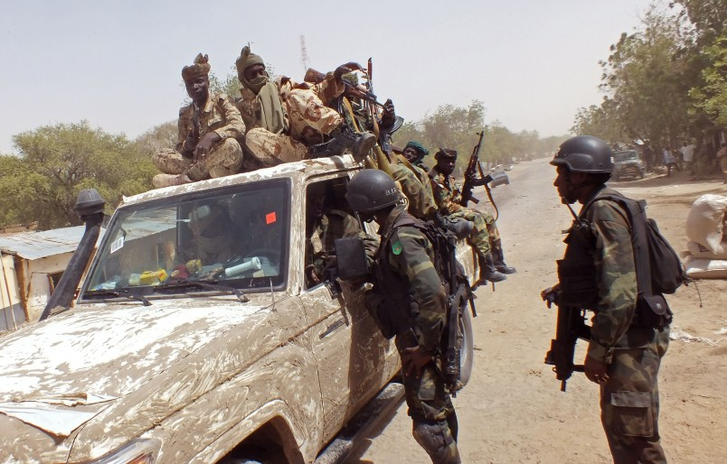 CORRECTS LOCATION WHERE PHOTO WAS TAKEN - In this photo taken on Thursday, Feb. 19, 2015, Chadian soldiers on top of a truck, left,  speak to Cameroon soldiers, right, standing next to the truck, on the border between Cameroon and Nigeria as they form part of the force to combat regional Islamic extremists force's including Boko Haram, near the town of  Fotokol, Cameroon. A girl suicide bomber as young as 10 blew herself up at a busy market in the northeastern Nigerian town of Potiskum on Sunday, Feb. 22, 2015, killing four others and seriously wounding 46 people, a witness and hospital records show.  (AP Photo/Edwin Kindzeka Moki)