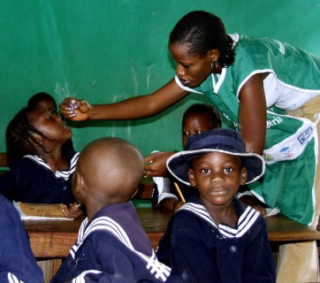 Health workers vaccinate children of the American Model school in their classroom with drops of polio vaccine in Lagos, Nigeria, February 24, 2004. Kano state governor Ibrahim Shekarau said on Saturday that it would not join an international polio immunisation campaign because of fears that the vaccine could cause infertility. REUTERS/George Esiri  THI - RTRDIJ1