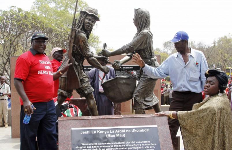 People gather near the sculpture  of the Mau Mau war veterans at Uhuru park during  the unveiling of the Mau Mau veteran memorial in Nairobi, Kenya, Saturday, sept ,12  2015 (AP Photo/Khalil Senosi)