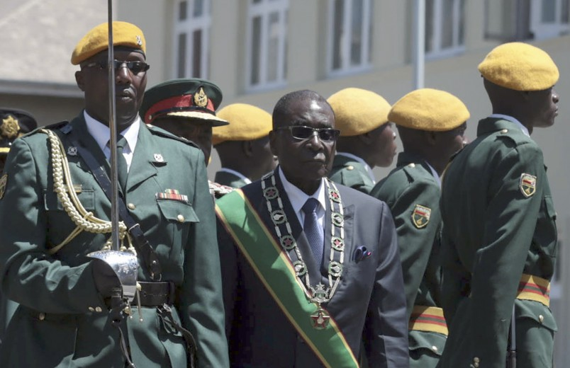 Zimbabwe President Robert Mugabe, center, inspects the guard of honor during the opening of Parliament in Harare, Zimbabwe, Tuesday, Sept. 15, 2015. (AP/Photo Str)