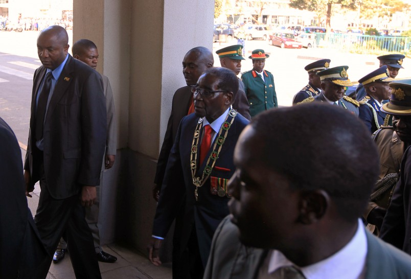 Zimbabwean President Robert Mugabe, center, arrives for his state of the nation address in Harare, Tuesday, Aug .25, 2015. Mugabe said that the economy was on a path to recovery  despite the tough times many Zimbabweans are going through.(AP Photo/Tsvangirayi Mukwazhi)