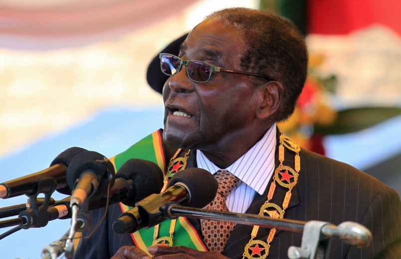 "FILE - In this Monday, Aug. 10, 2015 file photo Zimbabwean President Robert Mugabe delivers his speech during a ceremony to honour thousands of fighters who died in the 1970s Bush war  against colonialism, in Harare. Zimbabwe is ""frantically working"" to repatriate from Britain skulls of indigenous people killed in an 1890s anti-colonialism war, said a Cabinet minister. The state-run Herald newspaper Saturday quoted Home Affairs Minister Ignatius Chombo saying Zimbabwe will talk to its former colonial ruler over the skulls reportedly held by Britain's Natural History Museum. (AP Photo/Tsvangirayi Mukwazhi, File)"