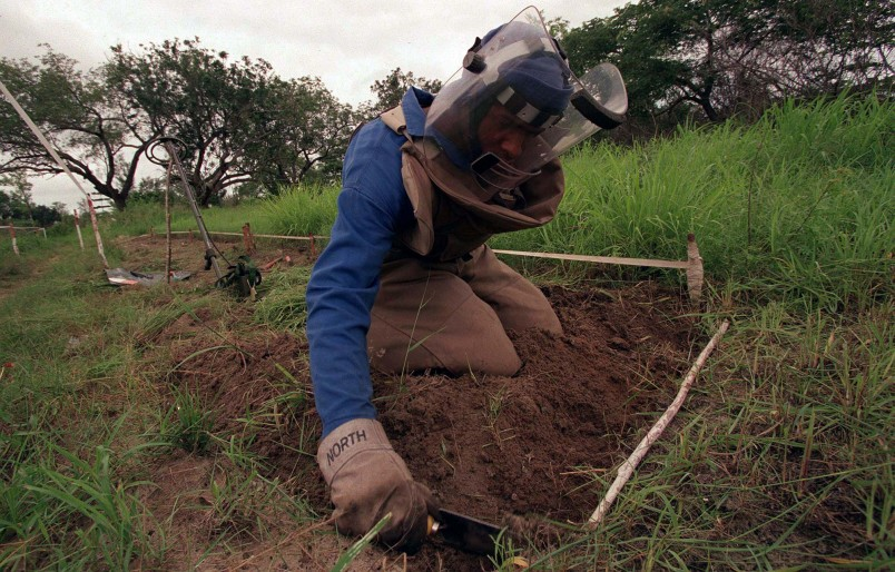 FILE - In this Dec. 3, 2001 file photo, former rebel soldier Abdul Momed Gofulof, clears land mines in Hnadane, 62 miles south of Maputo, Mozambique. The country plans to clear all known land mines with the help of backers by the end of this year, virtualy ridding its territory of a threat that caused casualties long after its civil war ended in 1992. (AP Photo/Themba Hadebe, File)
