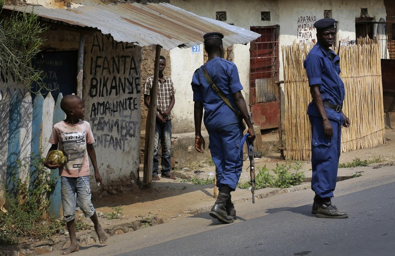 Police keep an eye on the crowds who gathered for the funeral procession of Emmanuel Ndere Yimana, an opposition supporter assassinated Wednesday July 21 2015, in Bujumbura, Burundi, Thursday July 22, 2015. Yimana is believed to be another victim of electoral violence targeting those opposed to president Pierre Nkurunziza's bid for a third term in office that opponents says is unconstitutional. Results for Tuesday's election will be announced Friday with Nkurunziza likely to win a third term after some opposition groups boycotted the polls and the main opposition figure Agathon Rwasa saying security forces frustrated his campaign.(AP Photo/Jerome Delay)