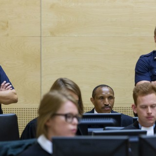 Bosco Ntaganda, center rear, a Congo militia leader known as The Terminator, waits for the start of his trial at the International Criminal Court on charges including murder, rape and sexual slavery allegedly committed in the eastern Ituri region of Congo from 2002-2003, in The Hague, Netherlands, Wednesday, Sept. 2, 2015. (Michael Kooren/Pool Photo via AP)