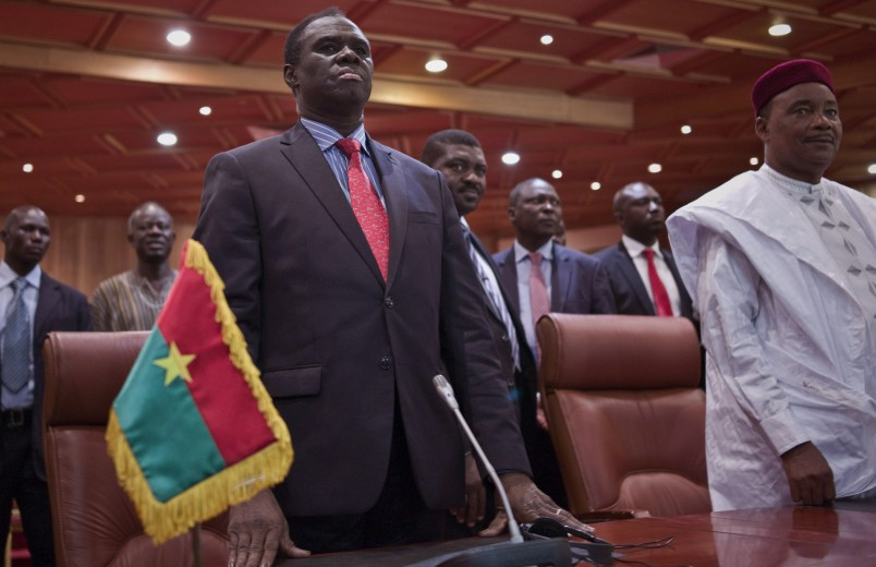 Burkina Faso's transitional president Michel Kafando, left, next to Niger's President, Mahamadou Issoufou, right, during a official handover ceremony  in Ouagadougou, Burkina Faso, Wednesday, Sept. 23, 2015. Amid cheers and the national anthem, Burkina Faso's interim president took charge of the country again Wednesday a week after a military general and his supporters overthrew him and his transitional government. Interim President Michel Kafando and Prime Minister Yacouba Isaac Zida marked their return to power in an official handover ceremony in Ouagadougou. (AP Photo)