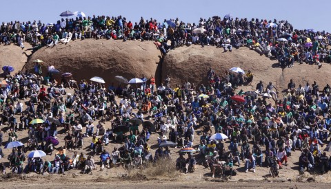 People attend a commemoration service for the striking platinum miners that were killed a year ago, in Marikana, South Africa, Friday Aug. 16, 2013.  It was a hot dusty afternoon at the brown rock hills near South Africa's Lonmin PLC mine in Marikana when South Africa was forced to face another bloody event in its long history of apartheid and state violence. Police opened fire a year ago on striking miners who carried sticks and homemade spears, killing 34. The details of Aug. 16, 2012 are still unsettled a year later in the small, impoverished community of Marikana, in South Africa's mineral-rich northwest.  (AP Photo/Denis Farrell)
