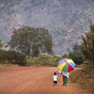A mother reaches out to hold the hand of her young daughter, as they walk home after a church service in the village of Rwinkwavu, near to Akagera National Park, in Rwanda Sunday, Sept. 6, 2015. (AP Photo/Ben Curtis)