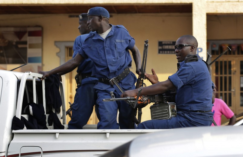 Police drive by the scene of a grenade attack on a parked car downtown Bujumbura, Burundi, Monday July 20, 2015, on the eve of presidential elections. No injuries were reported. Burundi has been rocked by violence that has left more than 100 people dead. Over 144,000 people have fled the country since the ruling party announced President Pierre Nkurunziza's candidacy in April. (AP Photo/Jerome Delay)