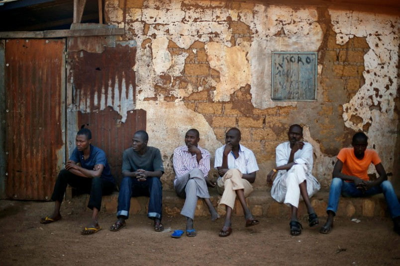 Muslim men sit outside a mosque in Bangui, Central African Republic, Saturday, Dec. 14, 2013. More than 600 people have been killed over the past 10 days in sectarian fighting in Central African Republic as the UN suspends its food distribution to over 40,000 IDPs by the airport for security reasons.  (AP Photo/Jerome Delay)