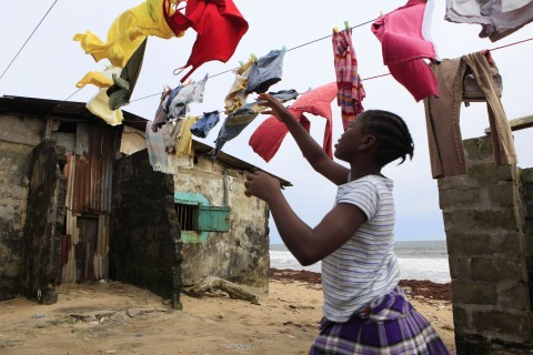 A girl takes down laundry hung on lines between homes partially  washed away in August, in a densely populated beachfront community suffering from coastal erosion, in the Sinkor neighborhood, Monrovia, Liberia Friday, Oct. 14, 2011. Liberia's electoral commission announced Friday that incumbent Ellen Johnson Sirleaf was ahead with 265,883 votes, or 45.5 percent of the ballots counted so far. But she had fallen short of the majority needed to win the election outright. (AP Photo/Rebecca Blackwell)