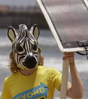 A protestor holds up a solar panel during a climate change summit held in the city of Durban, South Africa, Friday, Dec. 2, 2011. At a time of deep concern over global warming, a group of scientists, philosophers and legal scholars examined whether human intervention could artificially cool the Earth and what would happen if it did. A report discussed Friday at the U.N. climate conference in South Africa said that in theory reflecting a small amount of sunlight back into space before it strike's the Earth's surface would have an immediate and dramatic effect. But no one knows what the side effects would be. (AP Photo/Schalk van Zuydam)