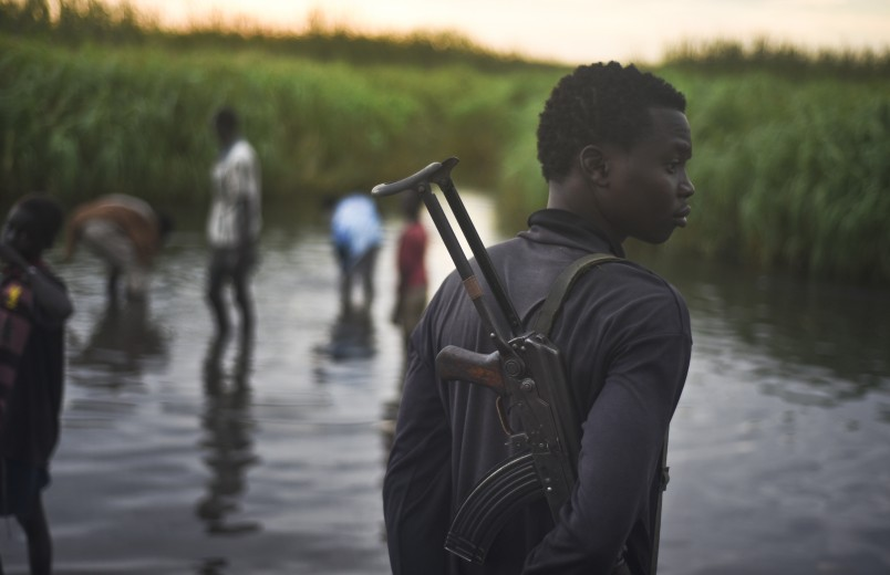 In this photo taken Monday, Oct. 12, 2015, an unidentified man with a gun stands watch over displaced people, who have taken shelter from fighting, in a rebel-held part of Leer county, in Unity State, South Sudan. Kok Island in Unity State has become a place of misery, with hundreds of war-weary people reaching there to seek shelter from the violence, just some of the more than 2 million displaced by South Sudan's civil war, which continues despite a peace accord signed in August. (AP Photo/Jason Patinkin)