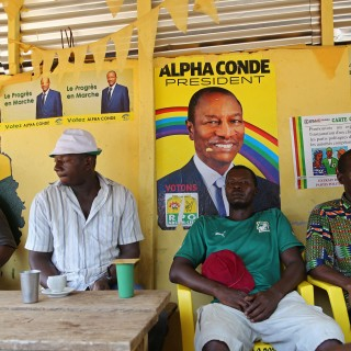People sit inside a local restaurant displaying posters for Guinea's incumbent President Alpha Conde, in Conakry, Guinea, Saturday, Oct. 17, 2015, Guinea President Alpha Conde is far ahead of his closest competitor in his bid for re-election and could garner enough support to avoid a runoff, according to preliminary results available Saturday.  (AP Photo/Youssouf Bah)