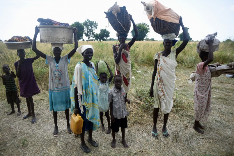 Women stand with their children and belongings in rebel held Bauw village in Koch county of South Sudan's Unity state, Friday, Sept. 25, 2015. Swampy, oil-rich Koch County bore the brunt of a government offensive launched in late April. The army and its allied militias raped and murdered civilians and burned villages in that campaign, according to the U.N. Now the government controls most towns in the area and the rebels operate from the countryside. (AP Photo/Jason Patinkin)  . .