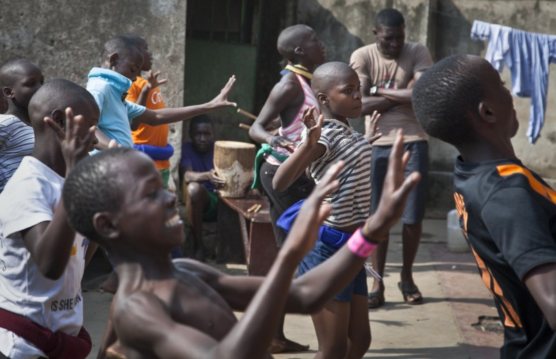 In this photo taken Sunday, Nov. 9, 2014, a dozen children perform a traditional courtship dance from eastern Uganda as part of a platform for changing attitudes among youth using dance, drama and popular hip hop music, at the Treasure Life Center in the Kamwokya slum of Kampala, Uganda. As World AIDS Day is marked on Dec. 1, Uganda and many other African countries are continuing their battle against HIV and AIDS, and Ugandan street activists like 26-year-old Hood Katende are trying to use music and drama to stem a troubling resurgence of HIV, which now infects more than 500 young women between the ages of 15 and 24 each week, according to the Uganda AIDS Commission. (AP Photo/Rebecca Vassie)