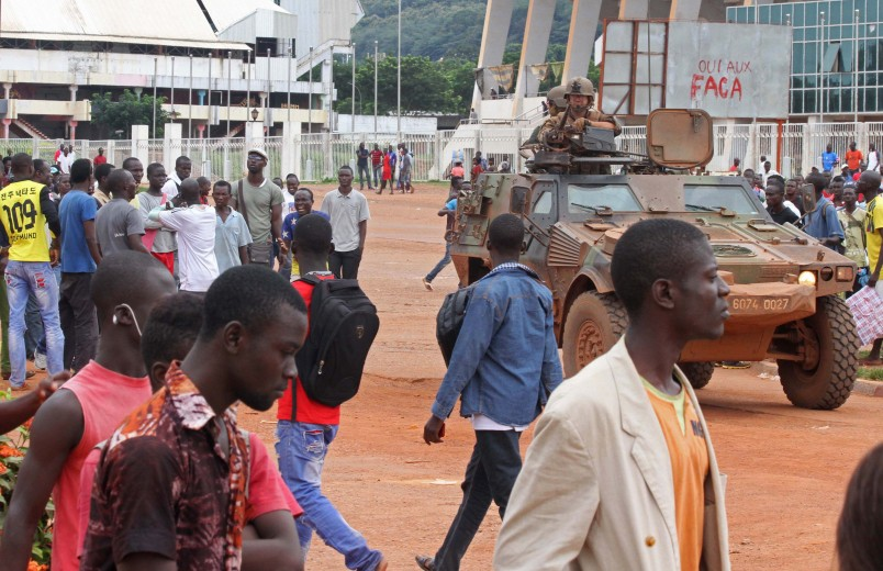 French peacekeeping soldiers, center right, patrol the city of Bangui, Central African Republic, Wednesday, Sept. 30, 2015.  42 deaths have been confirmed in Bangui since sectarian clashes erupted on Saturday between rivaling Christian and Muslim militias, but it is too dangerous for aid organizations to collect the bodies or help the wounded, according to Antoine Mbao-Bogo of The Red Cross.  Graffiti in background against the FACA Central African Armed Forces. (AP Photo)