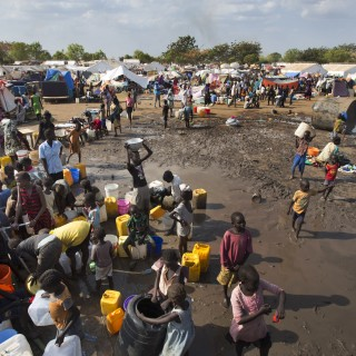 FILE - In this file photo of Sunday Dec. 29, 2013 file photo,  displaced people gather around a water truck to fill containers at a United Nations compound which has become home to thousands of people displaced by the recent fighting, in the capital Juba, South Sudan. One year after mass violence broke out in South Sudan, battles between government forces and rebel fighters continue, and aid officials say the international community must help residents stave off mass hunger.(AP Photo/Ben Curtis, File)
