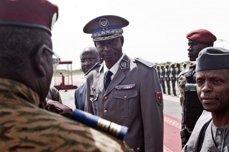 FILE - In this Wednesday Sept. 23, 2015 file photo, Burkina Faso coup leader Gen. Gilbert Diendere, center, greets people at the airport during the arrival of Niger's President Mahamadou Issoufou for talks in Ouagadougou, Burkina Faso. Burkina Faso's army took over the barracks of the presidential guard that carried out a short-lived coup this month, barraging them with gunfire Tuesday, Sept. 29, 2015 after they refused to disarm, the government said. Gen. Gilbert Diendere, who led the coup earlier this month but handed power back last week, called on his followers to lay down arms. (AP Photo, File)