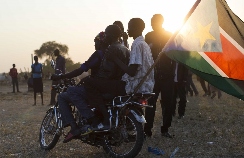 Youths ride three on a motorcycle as they celebrate after the result of an unofficial vote was announced in the disputed border region of Abyei Thursday, Oct. 31, 2013, whose ownership is claimed by both Sudan and South Sudan. The outcome of the unofficial vote announced Thursday was that residents of the disputed area between Sudan and South Sudan said they want to join South Sudan, which is no surprise since the residents who voted beginning Sunday are aligned with South Sudan. (AP Photo/Mackenzie Knowles-Coursin)