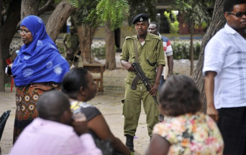 Armed Tanzanian police stand guard outside a vote counting center at Maji Matitu Primary School in Mbagala, in the Temeke district of Dar es Salaam, Tanzania Wednesday, Oct. 28, 2015. Tanzanians voted on Sunday in a presidential race that is the most tightly contested since the country became independent in 1961, with the ruling party being challenged by a former member who was recently the country's prime minister. (AP Photo/Khalfan Said)
