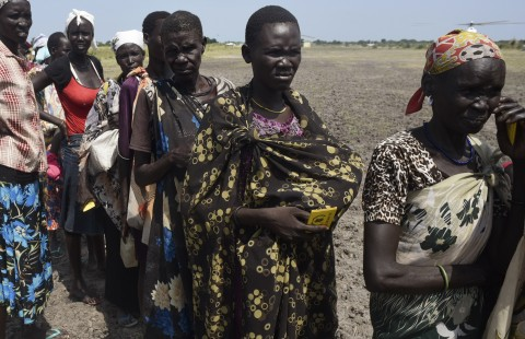 People queue for food being distributed of Koch, Unity state, South Sudan, Friday, Sept. 25, 2015. The regional bloc that mediated South Sudan's peace agreement says both sides have violated the deal signed last month. (AP Photo/Jason Patinkin)