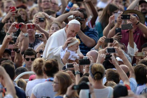 Pope Francis blesses a child as he greets the crowd before his general audience at St Peter's square on October 7, 2015 at the Vatican. Photo AP