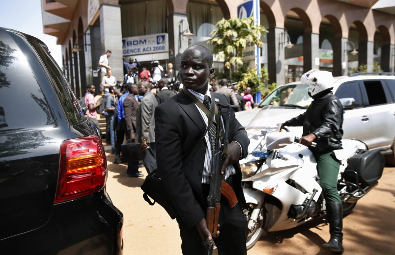"""Tight security surrounds Malian  President Ibrahim Boubacar Keita as he addresses reporters outside  the Radisson Blu hotel in Bamako, Mali, Saturday, Nov. 21, 2015. Malian security forces were hunting """"more than three"""" suspects after a brazen assault on a luxury hotel in the capital that killed 20 people plus two assailants, an army commander said Saturday. (AP Photo/Jerome Delay)"""