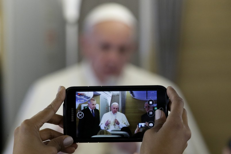 Pope Francis is framed in a smartphone as he greets journalists on board the flight to Nairobi, Kenya, Wednesday, Nov. 25, 2015. Pope Francis is traveling to Africa for a six-day visit that is taking him to Kenya, Uganda and the Central African Republic. (AP Photo/Andrew Medichini)