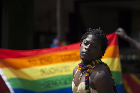 A transgender Ugandan poses in front of a rainbow flag during the 3rd Annual Lesbian, Gay, Bisexual and Transgender (LGBT) Pride celebrations in Entebbe, Uganda, Saturday, Aug. 9, 2014.  Scores of Ugandan homosexuals and their supporters are holding a gay pride parade on a beach in the lakeside town of Entebbe. The parade is their first public event since a Ugandan court invalidated an anti-gay law that was widely condemned by some Western governments and rights watchdogs. (AP Photo/Rebecca Vassie)