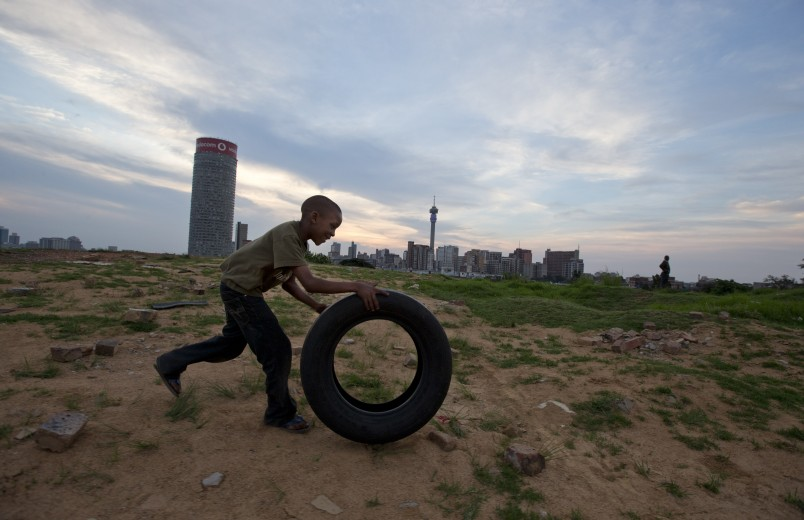 A boy plays with a rubber tyre on a hill overlooking the city of Johannesburg, South Africa, Saturday Dec. 7, 2013. Today's South Africa is no blissful paradise the nation struggles with a staggering rate of violent crime. It has the world's highest incidence of HIV infection. And it harbors an income inequality that would befit any feudal state. Still, its people made the transition from apartheid without all-out civil war. It is not only Africa's most successful economy, but also the 28th-largest in the world. Its democratic elections are widely believed to be fairly conducted. None of those successes was pre-ordained, and they were all given a major assist by the preternatural spirit of one man: Nelson Mandela. (AP Photo/Peter Dejong)
