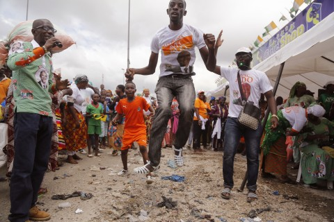 A man jumps in the air as he and others react at a local market area to celebrate the victory of Ivory Coast's President Alassane Ouattara after elections in  Abidjan, Ivory Coast, Wednesday, Oct. 28, 2015.  Ivory Coast's President Alassane Ouattara easily won re-election in the first vote since a disputed poll five years ago sparked violence that killed thousands in the West African economic powerhouse, the electoral commission announced early Wednesday. (AP Photo/Schalk van Zuydam)