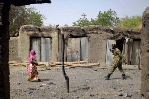 A Chadian soldier and a woman walk past burned stores in the Lake Chad shore village of  N'Gouboua Thursday, March 5, 2015. Boko Haram militants arrived in N'gouboua before dawn on Feb. 13, marking the first attack of its kind on Chad. By the time the scorched-earth attack ended, they had burned scores of mud-brick houses by torching them with gasoline and had killed at least eight civilians and two security officers. Some 3,400 Nigerian refugees had been living in the village at the time of the attack, and all have since been relocated further inland. (AP Photo / Jerome Delay)