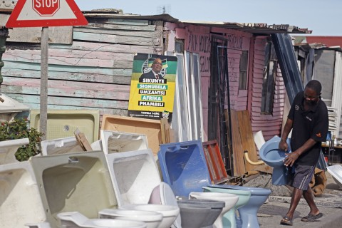 A man, right, who sells toilets, carries one next to a shack which has the face of South African President Jacob Zuma, center, on a poster,  in Khayelitsha Township on the outskirts of the city of Cape Town, South Africa, Tuesday, May 6, 2014. Some thousands of people still are considered to live under the poverty line 20-years after the first democratic elections, as South Africans go to the polls tomorrow. (AP Photo/Schalk van Zuydam)