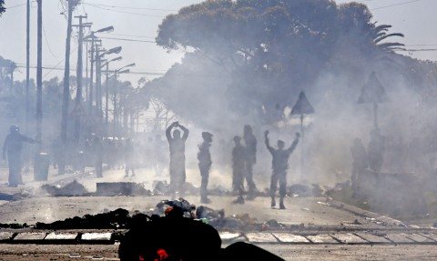 An electric pole and rubbish bins burns in the foreground, as Langa township residents protest, on the outskirts of the city of Cape Town, South Africa, Wednesday, July 9, 2014. Hundreds of Langa township residents protested against the lack of basic services provided by the local government including lack of toilets, running water, housing, and other basic needs. (AP Photo/Schalk van Zuydam)