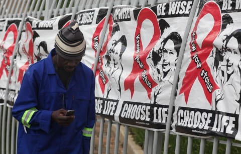 A man makes a call on a mobile phone as he passes past a World AIDS Day banners on the perimeter of an office building in Sandton, Johannesburg, South Africa, Monday, Dec. 1, 2014. About 2 million HIV-infected people are on government supplied ARV's with stigma related to the disease being a major issue according to the Treatment Action Campaign (TAC) who fought for the government funded drugs. (AP Photo/Denis Farrell)