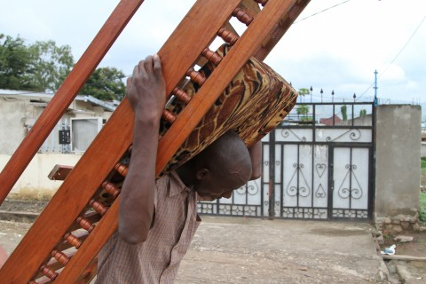 A man carries a chair frame on his back, in Bujumbura, Burundi, Saturday, Nov. 7, 2015. Carrying their prized possessions, scores of people fled Burundi's capital Saturday before a looming security crackdown that has left many predicting more bloody violence ahead.  (AP Photo)