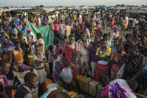 People wait to fill up water containers in Bentui, South Sudan, Wednesday, July 2, 2014. Preventable diseases and severe malnutrition are causing an alarming number of deaths among the estimates 45,000 people taking refuge at a UN base in Bentiu, South Sudan according to a recent MSF report. The report show that at least three children under 5 years old are dying per day, most from preventable diseases. (AP Photo/Matthew Abbott)