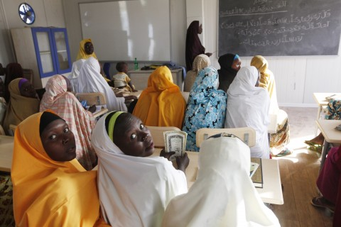 In this photo taken Monday, Dec. 7, 2015, children displaced by Boko Haram during an attack on their villages receive lectures in  a camp in Maiduguri, Nigeria. Attacks by Islamic extremist group Boko Haram in northeastern Nigeria and neighboring countries have forced more than 1 million children out of school, heightening the risk they will be abused, abducted or recruited by armed groups, the United Nations children's agency said Tuesday, Dec. 22, 2015. (AP Photo/ Sunday Alamba)