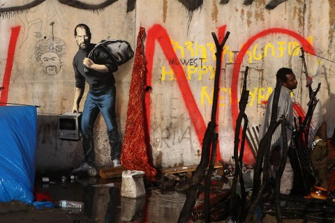 A painting by English graffiti artist Banksy is seen at the entrance of the Calais refugee camp in France, in Calais, northern France, Monday, Dec. 21, 2015. The elusive graffiti artist has depicted the late Apple guru Steve Jobs — whose biological father was from Syria — carrying a black garbage bag and an early model of the Macintosh computer. (AP Photo/Michel Spingler)
