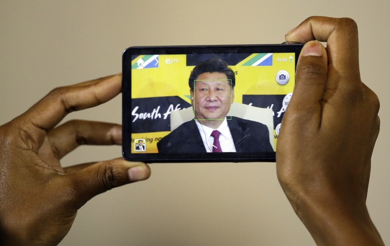 A journalist takes a photo of Chinese President Xi Jinping, using a mobile phone during a joint media conference with South African President Jacob Zuma, at Union Building Pretoria, South Africa, Wednesday, Dec. 2, 2015.  (AP Photo/Themba Hadebe)