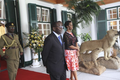 Zimbabwean President Robert Mugabe, center, and his wife Grace stand at State House in Harare, Saturday,  Jan., 23, 2016. Mugabe,91, who was rumored to be sick and hospitalized, returned from his annual vacation on Friday. (AP Photo/Tsvangirayi Mukwazhi)