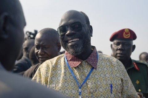 Ramadan Hassan Lako, the head of a delegation of South Sudan's armed opposition, smiles to a member of the government upon arrival to the country's capital Juba after two year's in exile on Monday, Dec. 21, 2015.  A fifteen member delegation arrived in Juba on December 21 in the first concrete step toward realizing a peace agreement signed two months ago to end South Sudan's civil war. (AP Photo/ Jason Patinkin)